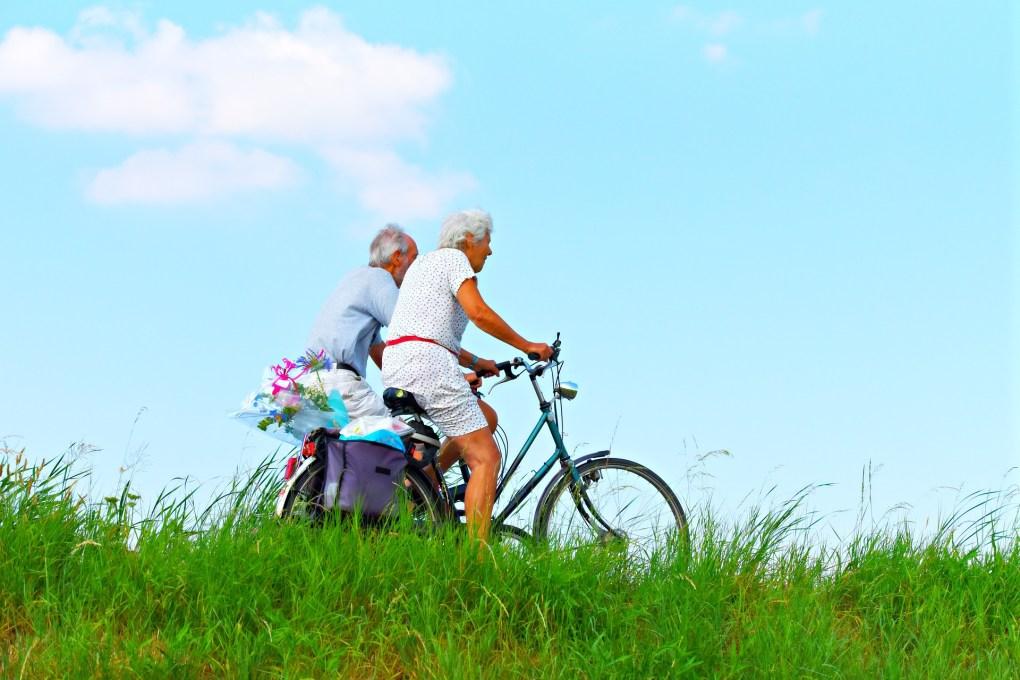 Imagem de um casal de idosos andando de bicicleta.