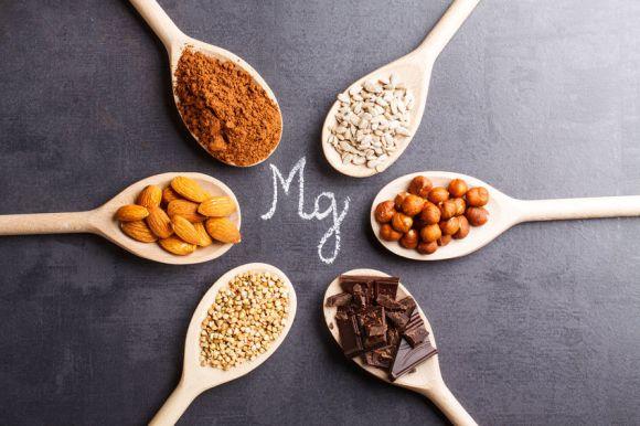 Colheiras com condimentos e semente e o símbolo do magnésio escrito no centro.