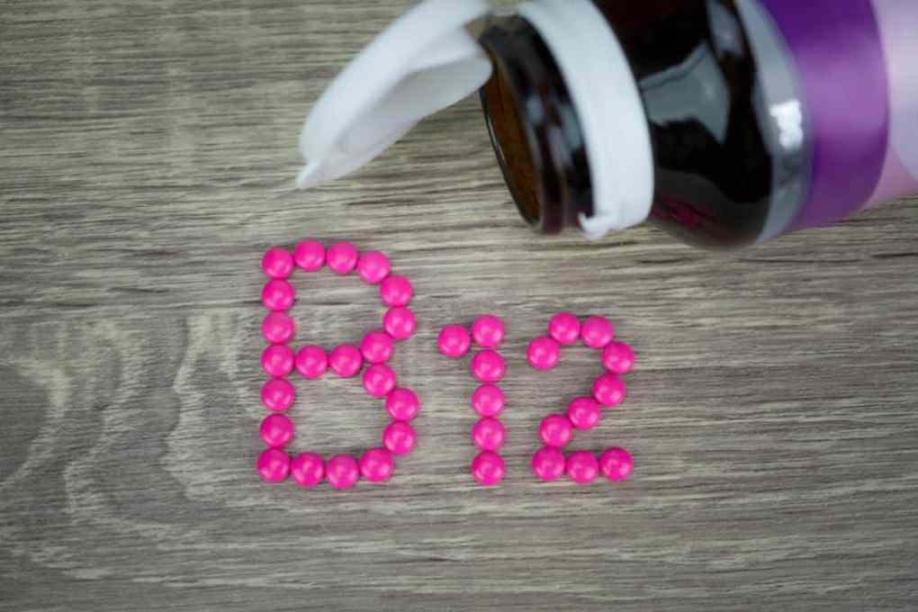 Comprimidos formando a sigla B12 com frasco ao lado.