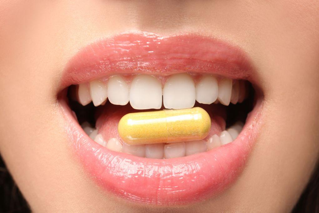Imagem de uma mulher como uma cápsula de vitamina entre os dentes.