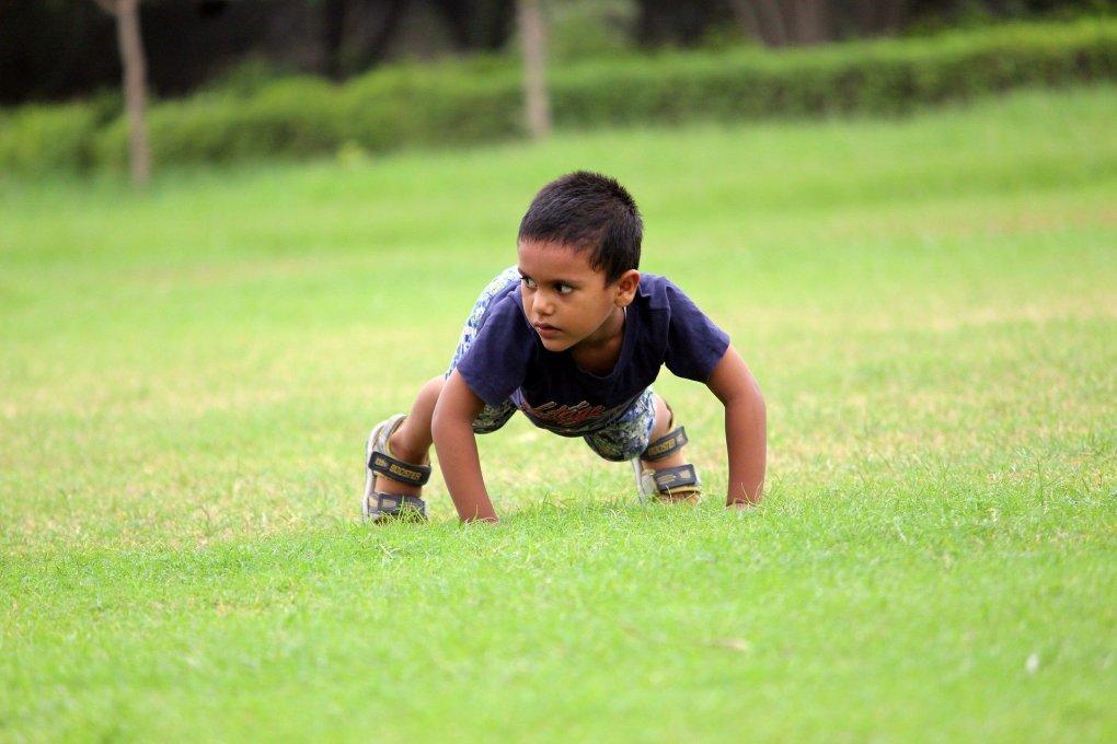 Imagem mostra uma criança em posição de exercício físico.
