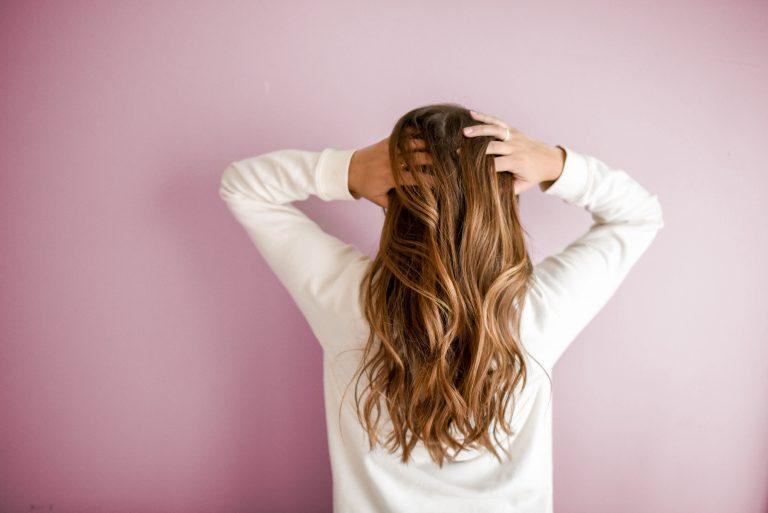 Mulher de costas com mãos nos cabelos.