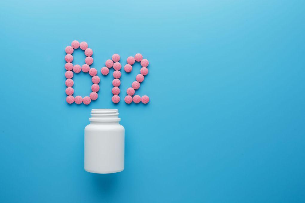 Comprimidos cor de rosa no formato da letra B12 em um fundo azul, derramados de uma lata branca. Conceito de suplementos dietéticos