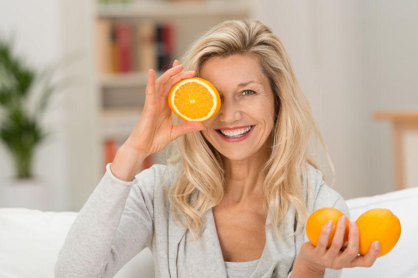 oudere vrouw die vitamine c consumeert