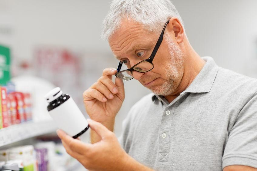 elder guy reading pills instructions