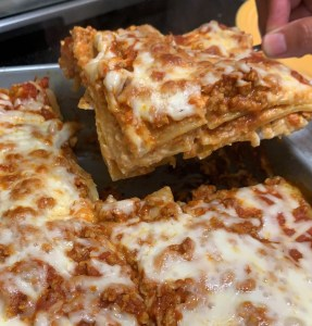 Haché lasagna with pasta sauce, noodles, and cheese.