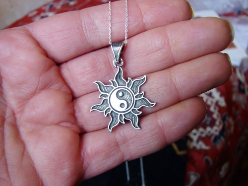 Pendant Yin Yang in rays of the Sun