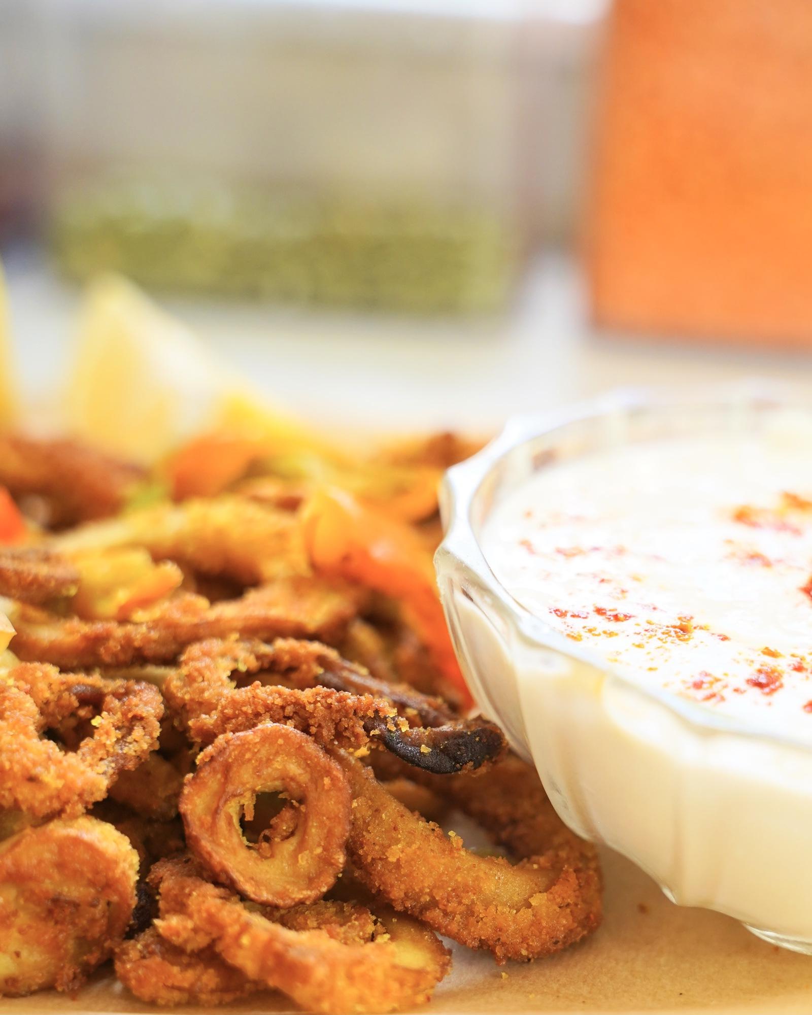 tiny fried calamari circles next to a bowl of garlic vegan mayonnaise