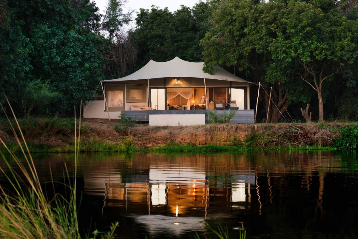 Sausage Tree Camp Luxury Suite on the amid the trees and along the water's edge