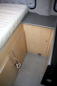 Toilet onder het bed en grote kast ernaast .
