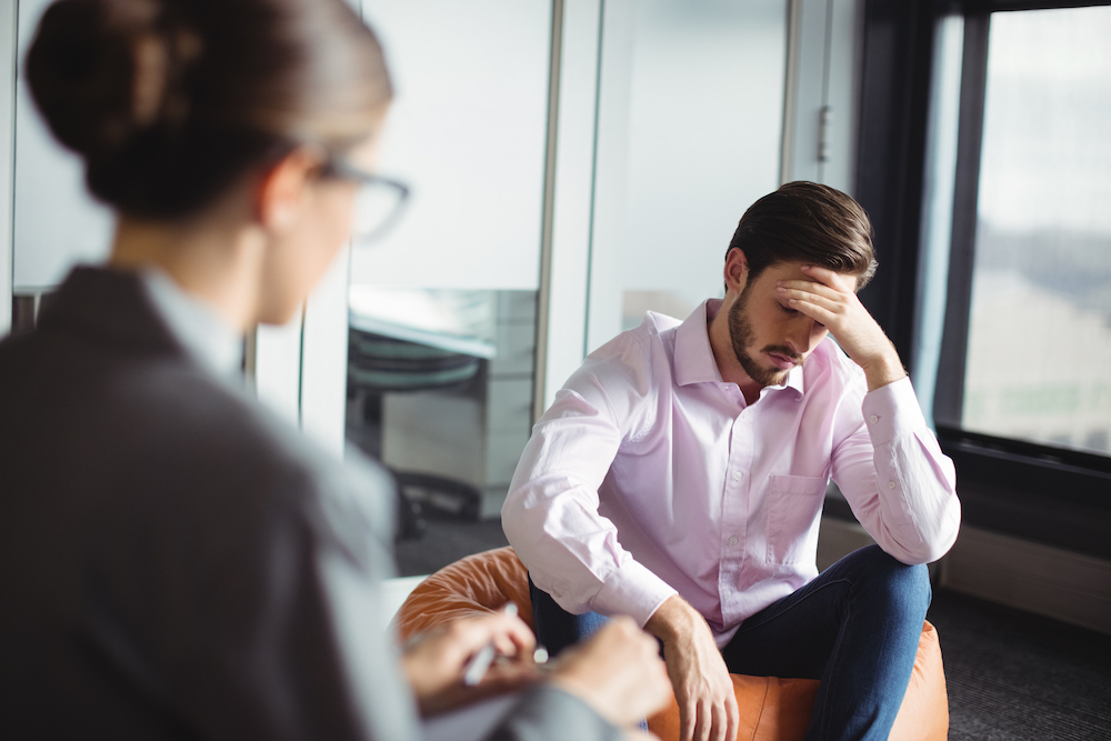 Unhappy man consulting counselor