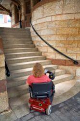Donna in carrozzina ai piedi di una scalinata