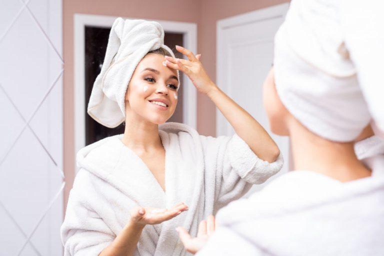 Donna allo specchio che si mette la crema