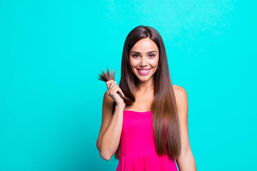 Donna sorridente con capelli nella mano