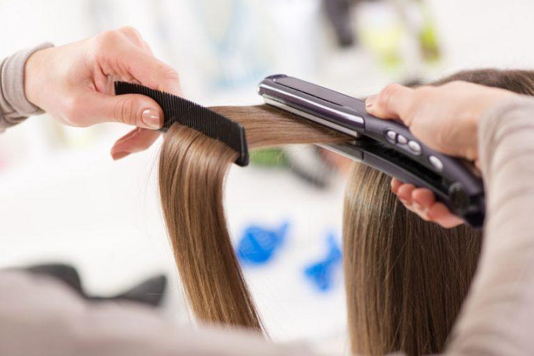 Parrucchiere che piastra i capelli