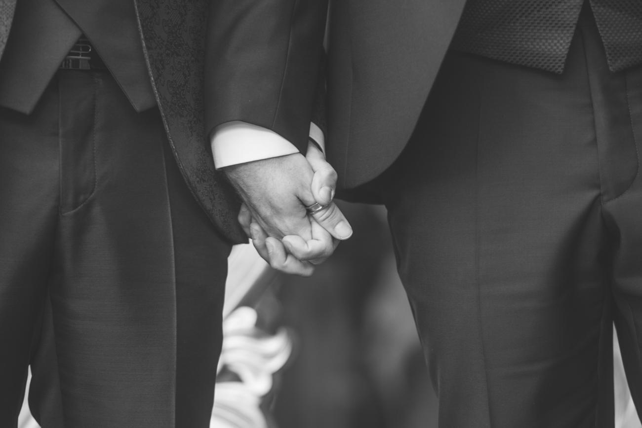 Detalle de novios gays cogiendose de la mano
