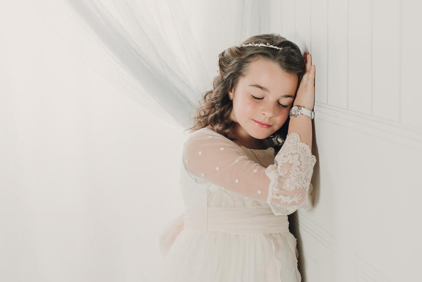 niña de comunion apoyada en pared