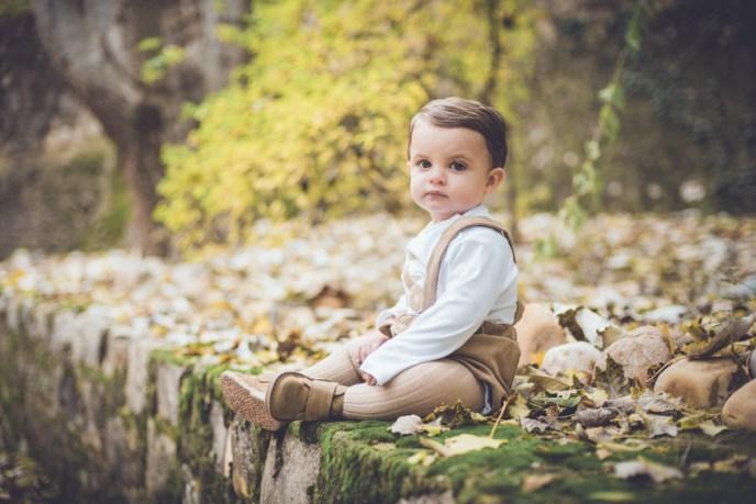 bebe sentado en el suelo entre hojas