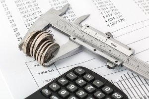 caliper measurement holding coins on top of financial journal with calculator on foreground