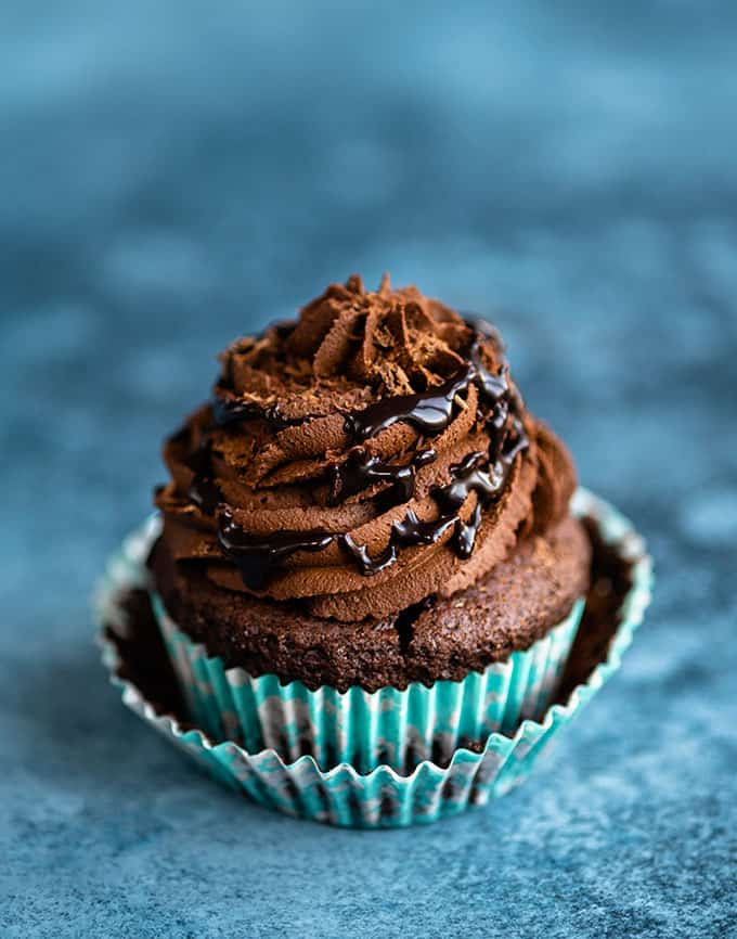 Vegan chocolate cupcake topped with ganache frosting and chocolate sauce