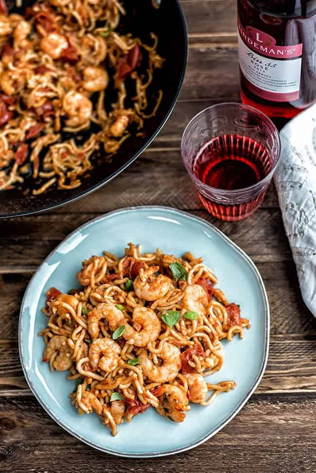 Plate of prawn noodles with a glass of rose wine on a rustic background