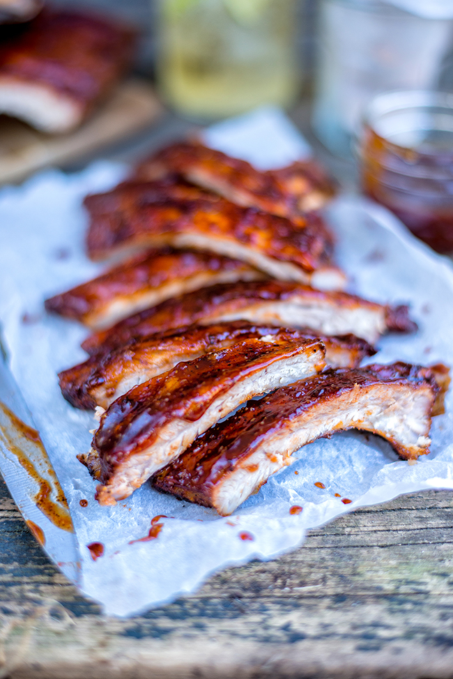These sticky dry-rubbed ribs with bourbon-spiked BBQ sauce are totally irresistible! Cook in the oven or your barbecue.