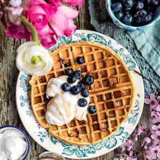 These buttermilk blueberry waffles are crisp on the outside and fluffy on the inside. Serve with whipped coconut cream for an indulgent breakfast.