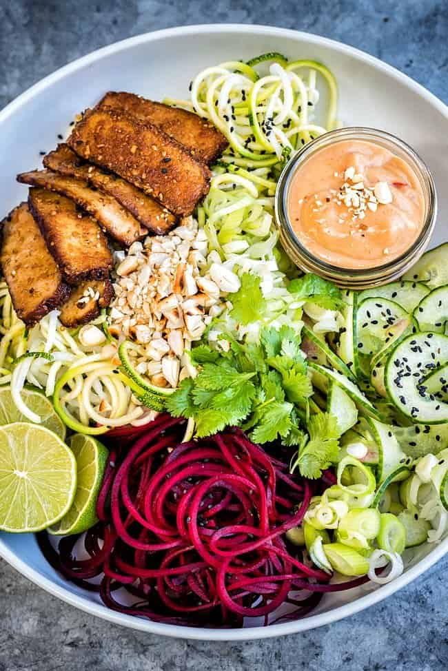 A medley of spiralized vegetable noodles with smoked tofu and spicy peanut sauce - a healthy and delicious vegan recipe.