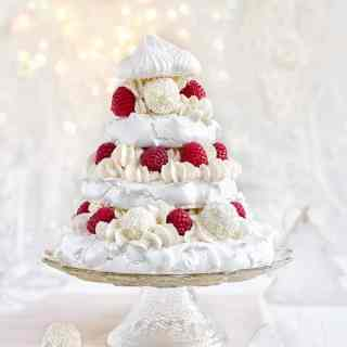 Meringue Christmas cake with whipped coconut cream, raspberries and white chocolate truffles