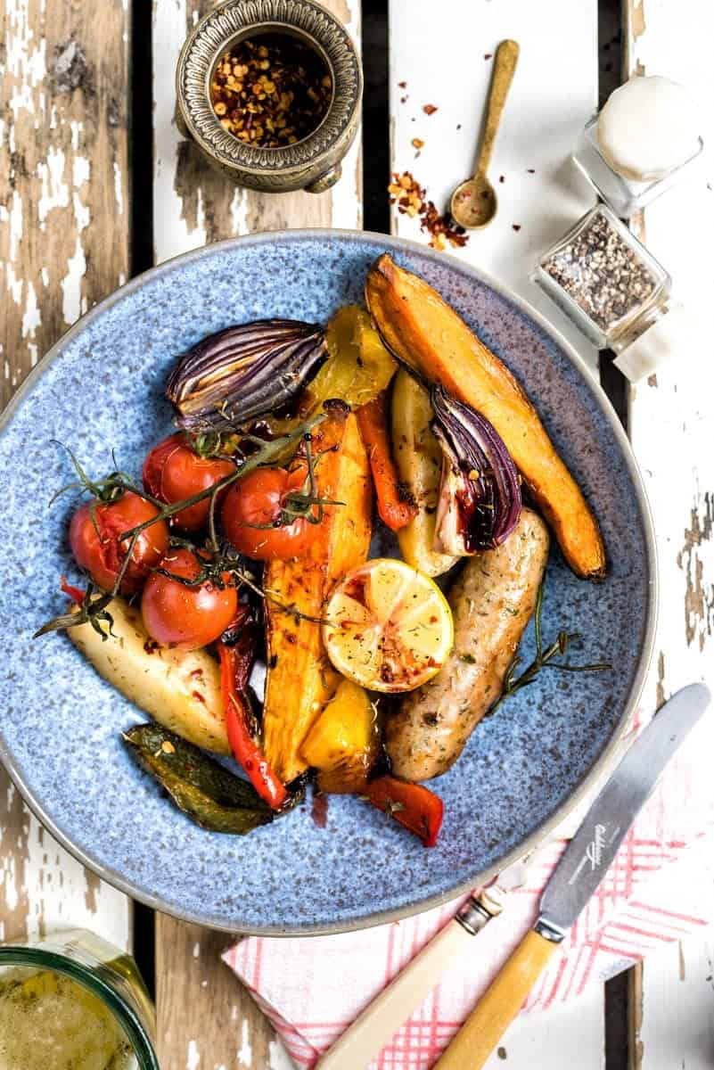 Easy sausage, potato and pepper traybake served in a blue bowl