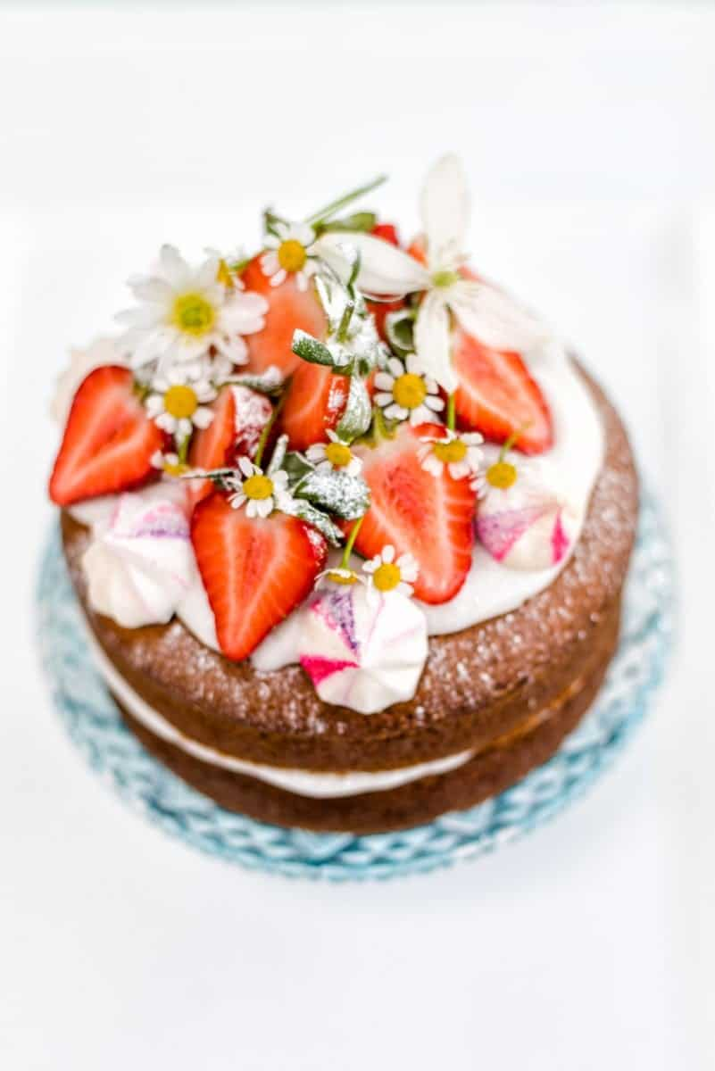 Vegan vanilla cake with whipped coconut cream – perfect for birthdays and celebrations and embarrassingly easy to make! Decorate with fresh strawberries and flowers.