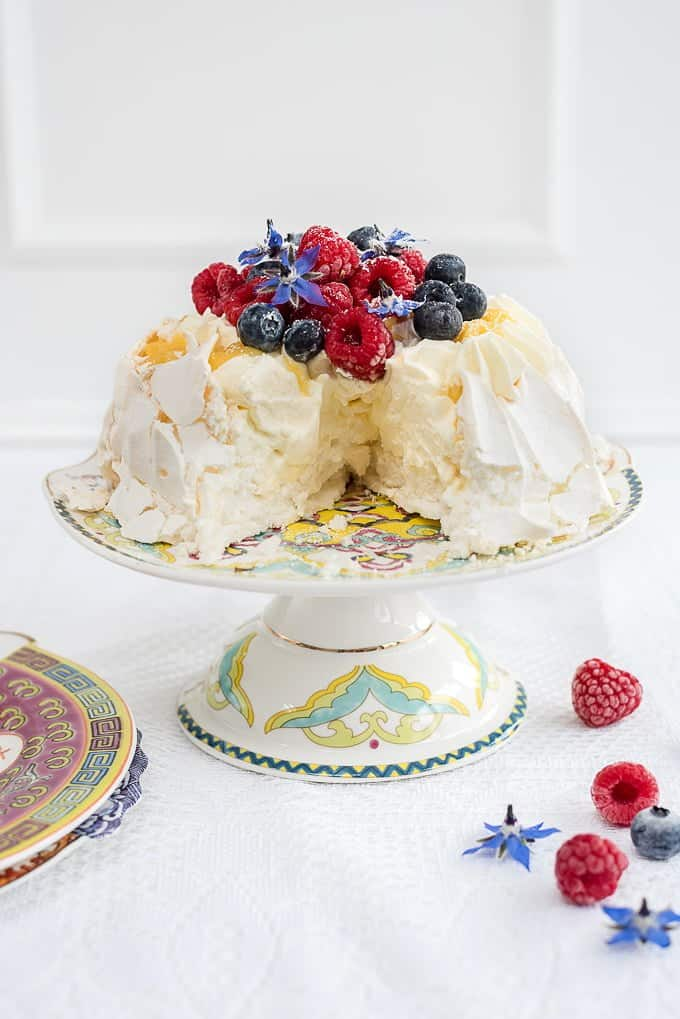 Pavlova crown with whipped cream, lemon curd and fresh berries