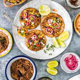 Tender and delicious bourbon and coke pulled pork served on tostadas with quick sweetcorn salsa and pickled onions. This recipe makes a big batch of pulled pork which you can serve in a variety of ways.
