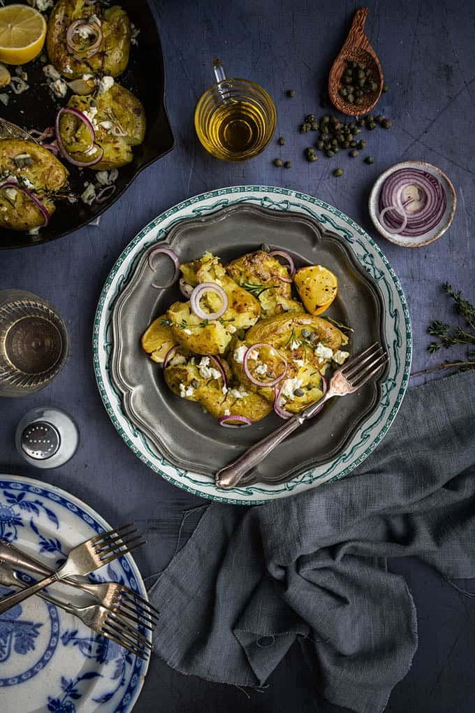 These Greek smashed potatoes are fantastic as a side dish, but can become a main meal if you add some puy lentils or some tinned tuna. The potatoes even taste great reheated the next day or you can turn leftovers into a salad. They are really an all-round winner.