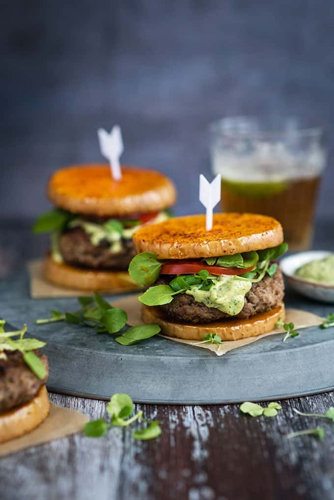 Herby lamb burgers with feta cheese served over butternut squash 'buns' with an addictive green tahini dressing