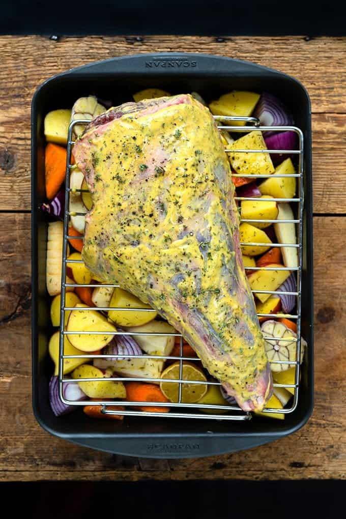 Mustard-rubbed leg of lamb on a roasting tray