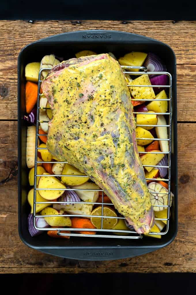 Mustard-rubbed leg of lamb on a roasting tray