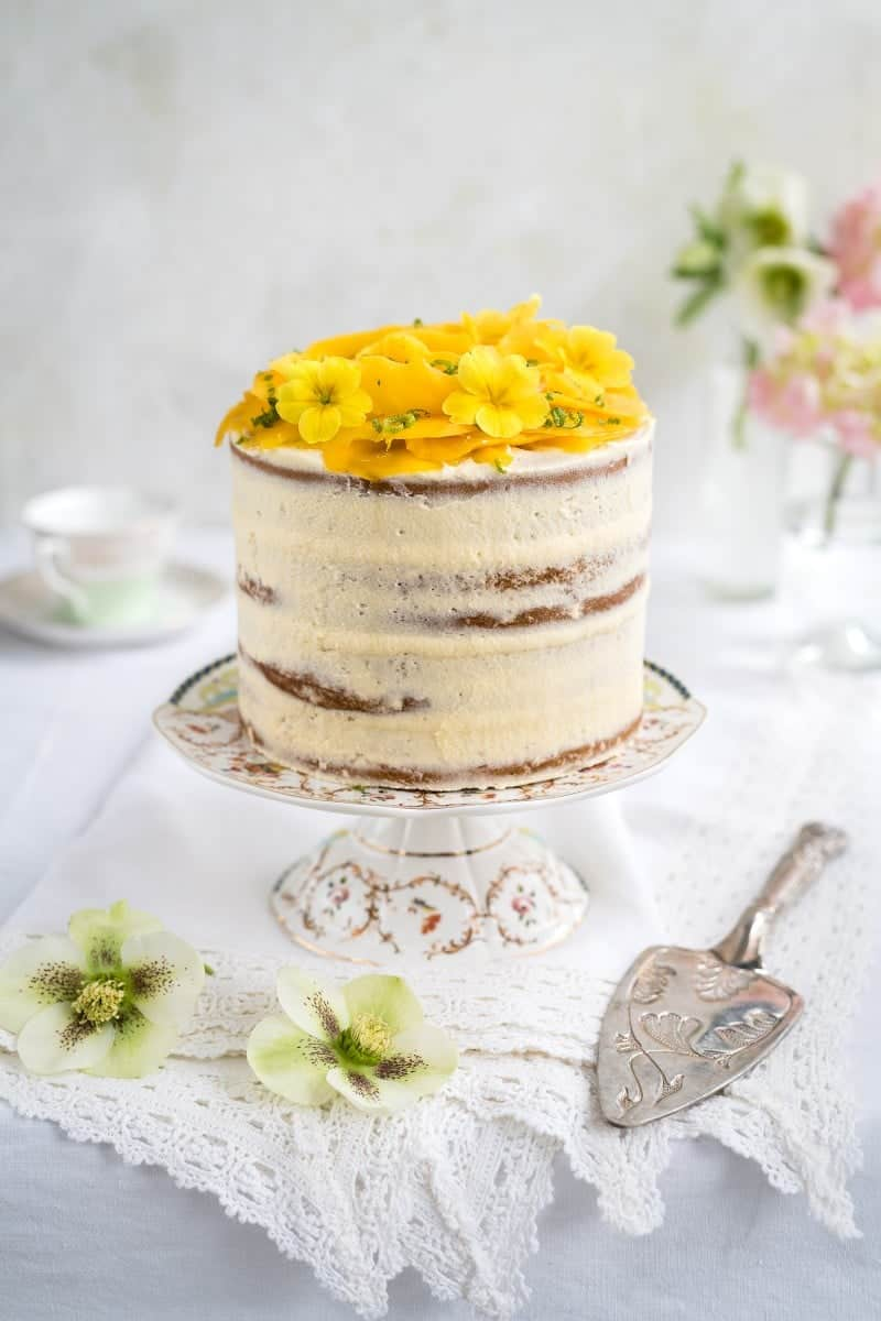 Tall Vegan Layer Cake Topped With A Mango Rose And Edible Flowers
