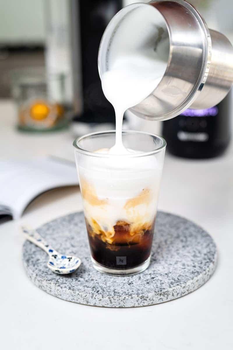Pouring milk foam onto a glass of Nespresso on Ice Macchiato