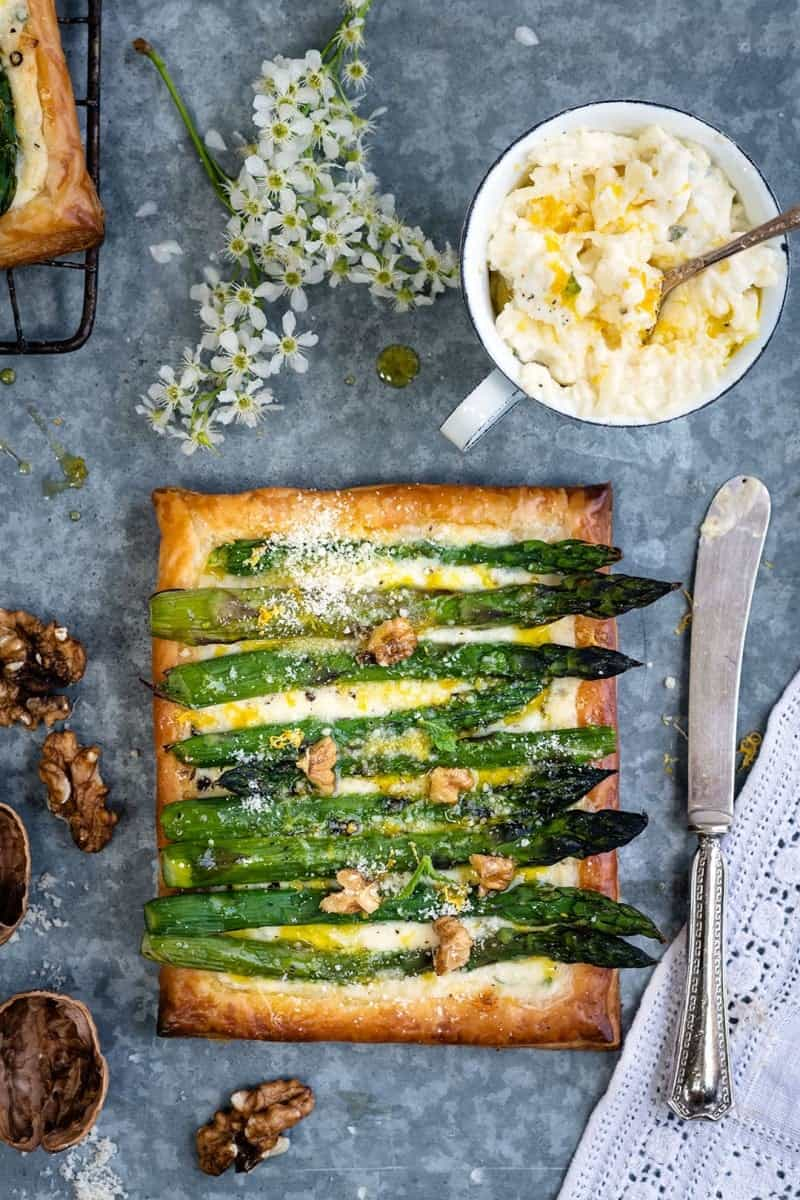 Puff pastry tart filled with cheese and topped with asparagus