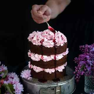Chocolate layer cake with blackberry buttercream with blackberry syrup drizzled over the top