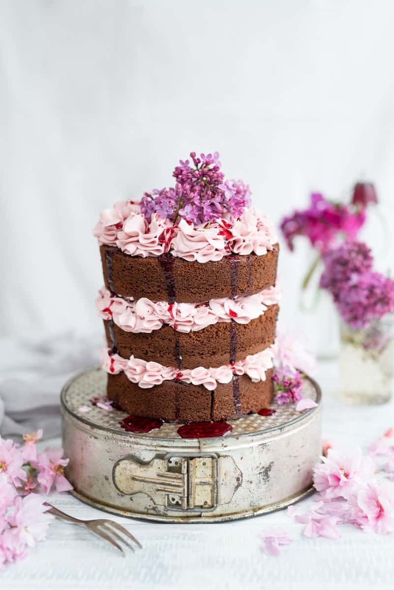 Chocolate layer cake on a cake tin, frosted with Italian buttercream and decorated with lilacs