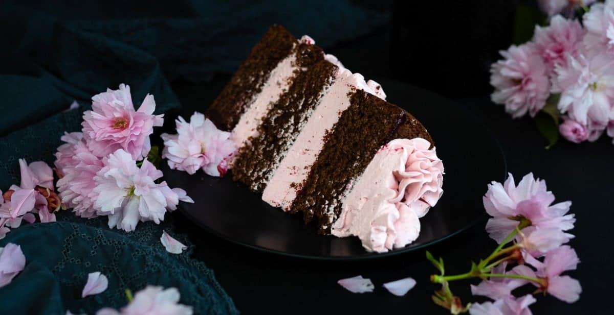 Slice of chocolate layer cake with blackberry Italian buttercream