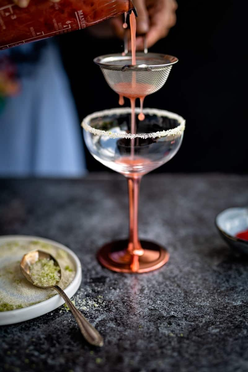 straining a strawberry gin sour into a coupe glass