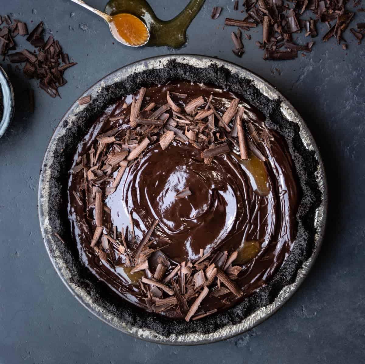 Decorating a no bake vegan chocolate tart with salted caramel and chocolate curls