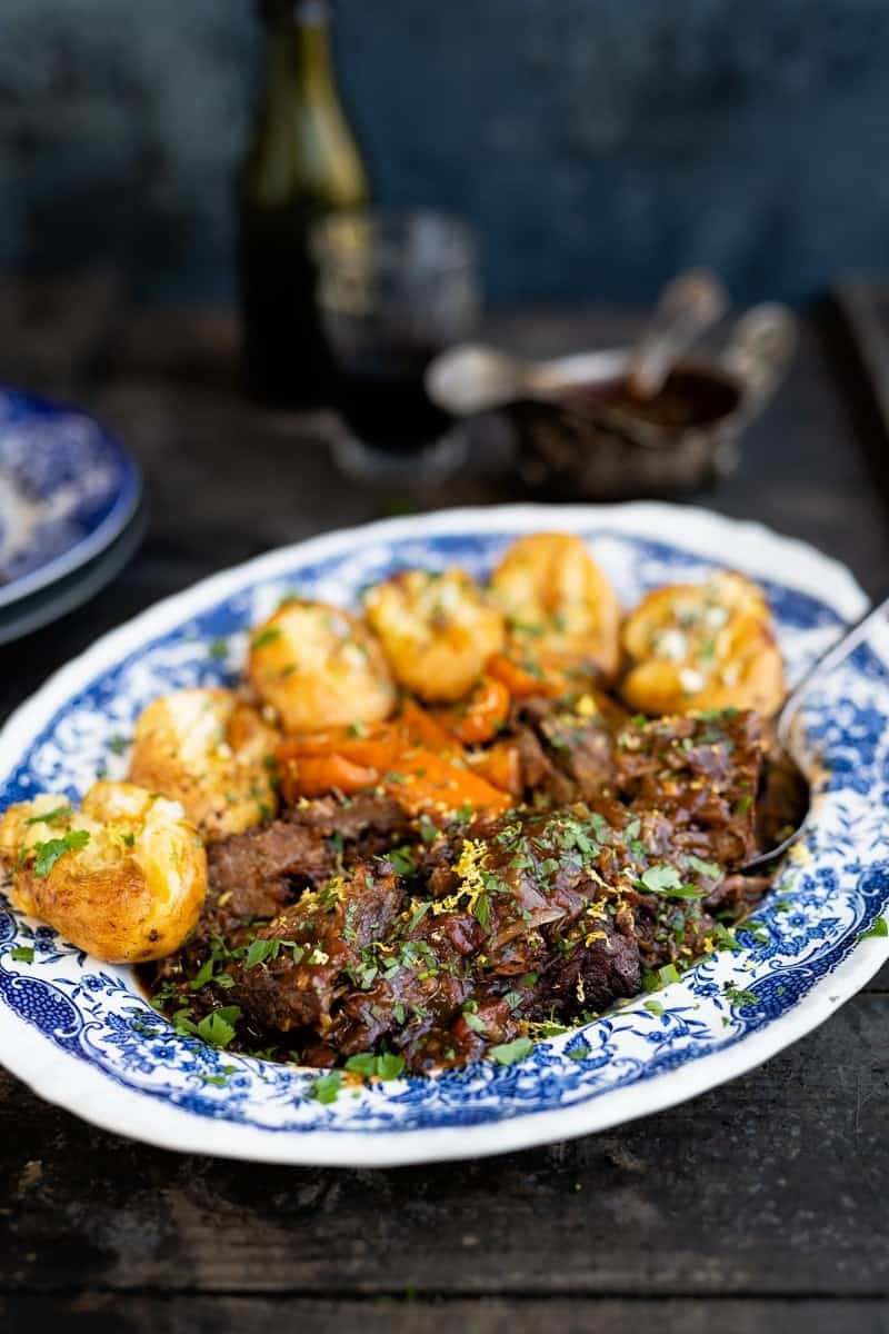 Beef brisket arranged on a blue platter with potatoes and carrots