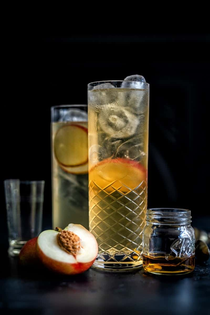 sparkling peach whisky cocktail in a tall glass garnished with peach slices