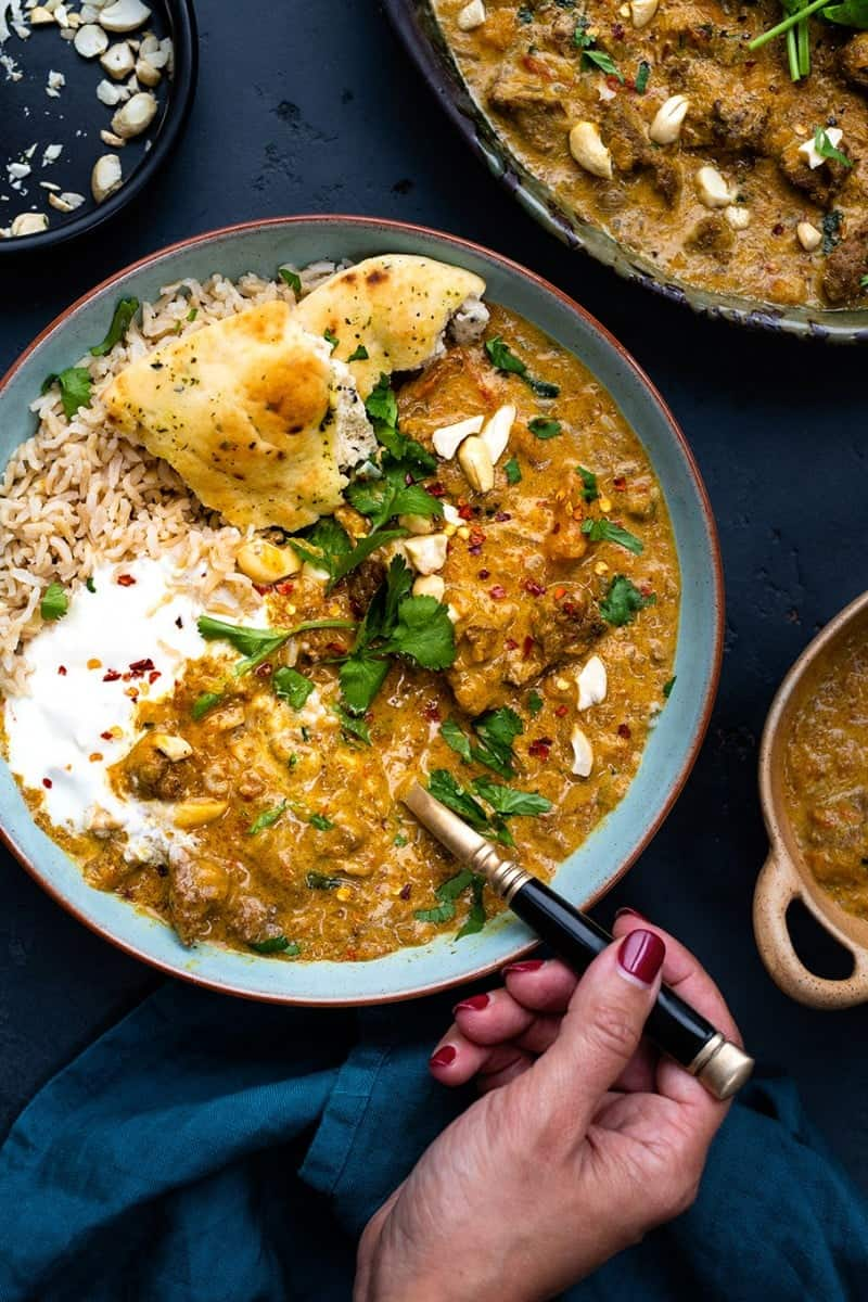 Lamb korma with rice and naan bread in a bowl