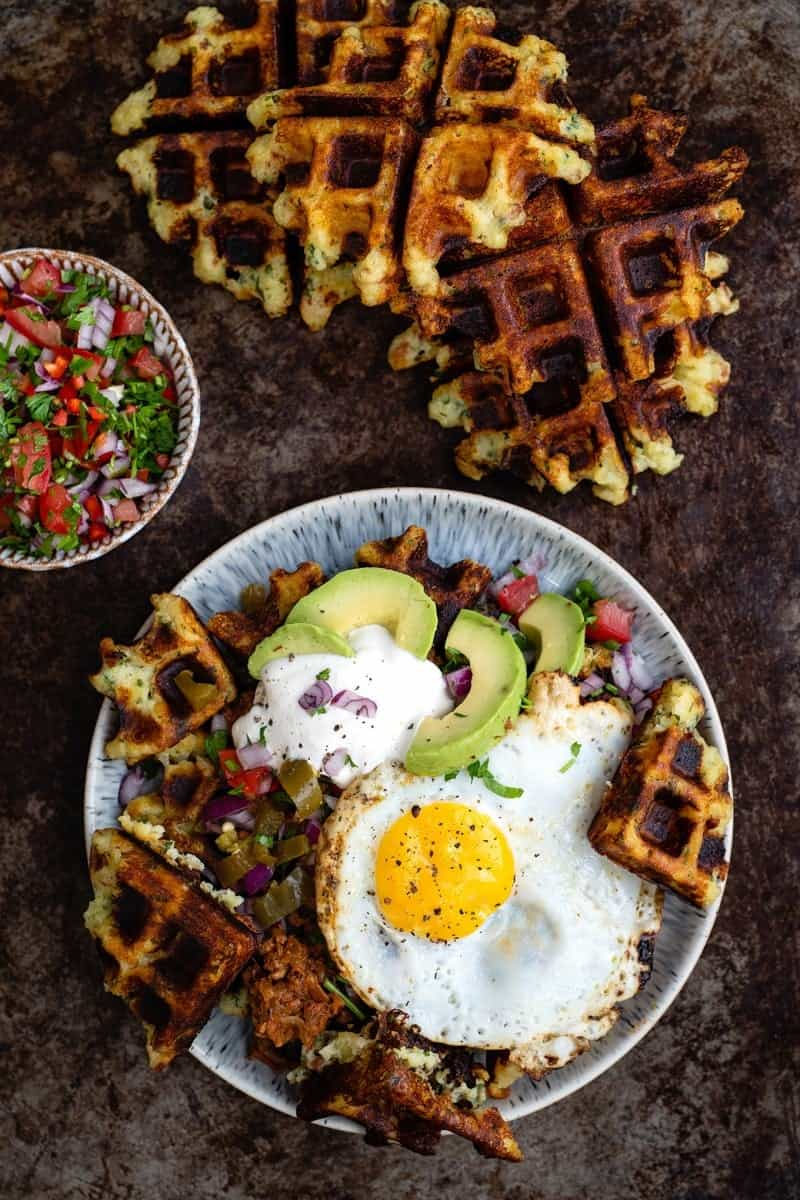 mashed potato waffles topped with egg, salsa, soured cream and avocado