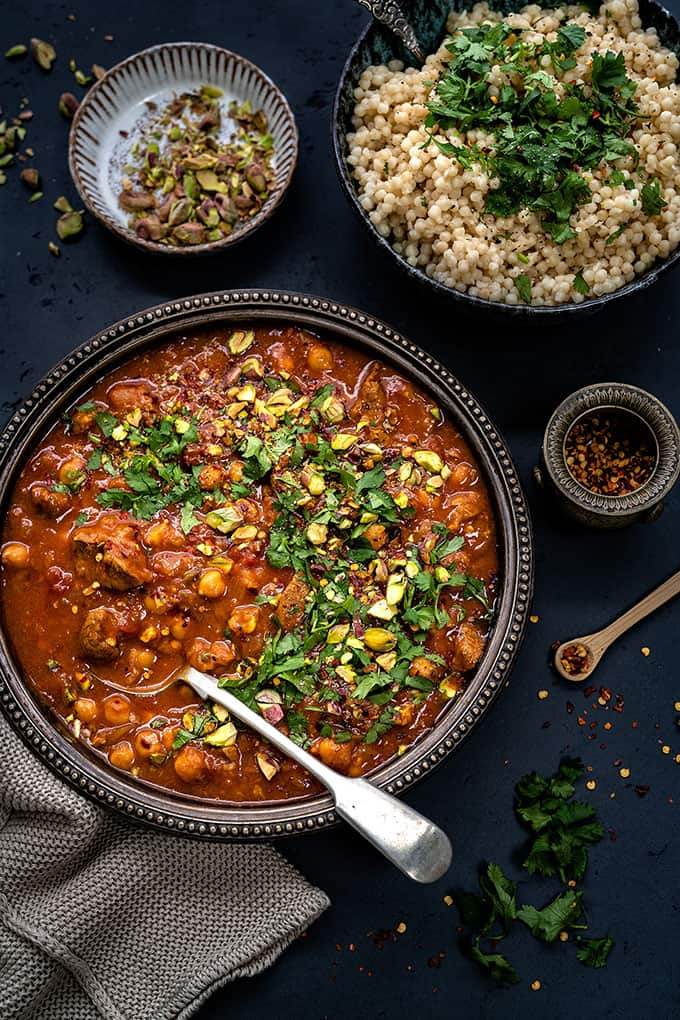 Overhead shot of lamb tagine in a rustic metal bowl with giant couscous on the side on dark background